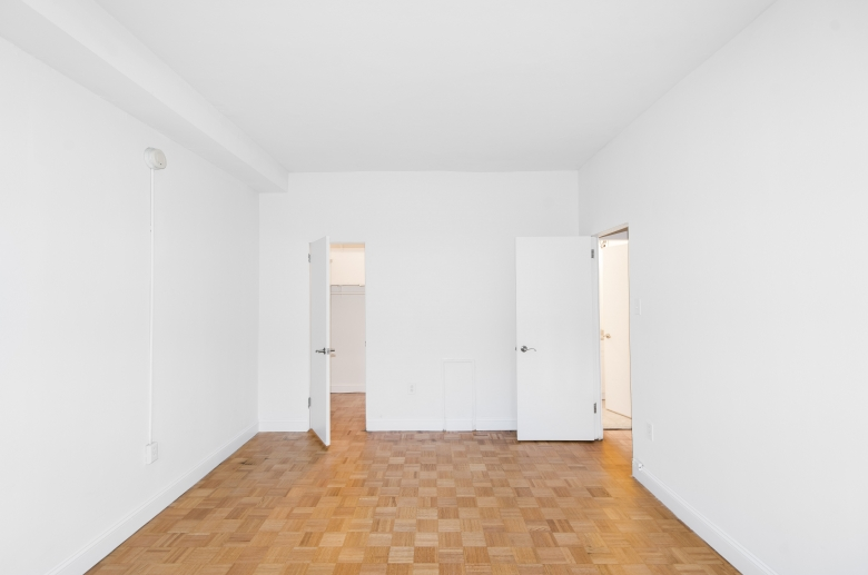Bedroom with hardwood floor and ample closet space