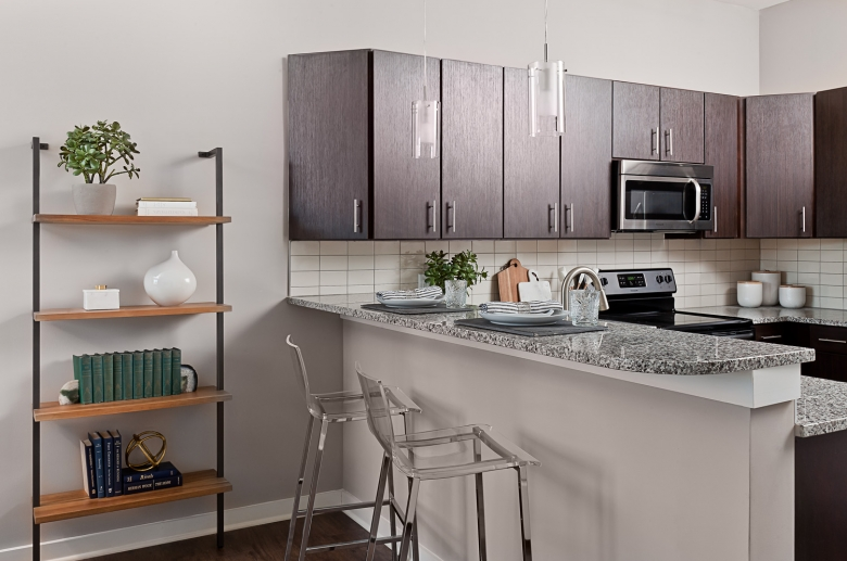 Fully-equipped kitchen with granite countertop, le backsplash, and stainless steel appliances