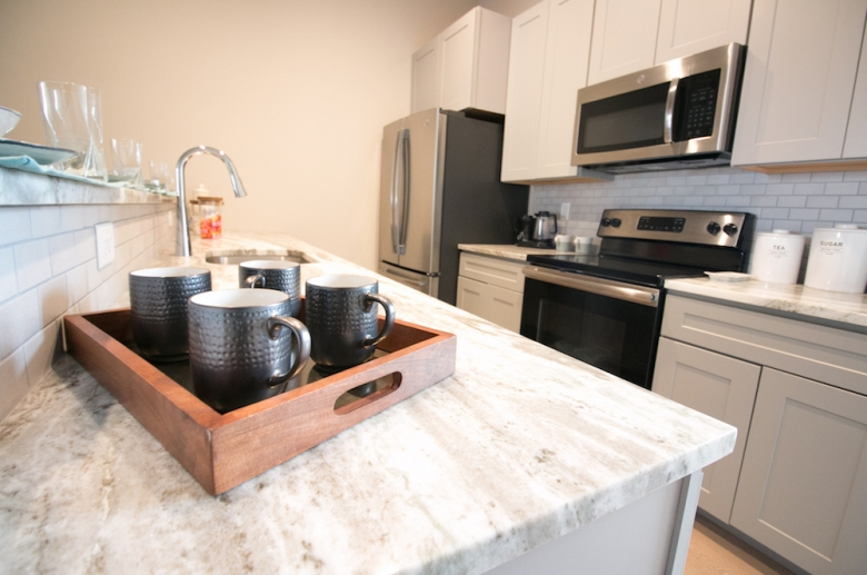 Fully equipped modern kitchen with stainless steel appliances at The Cottages at The Mills