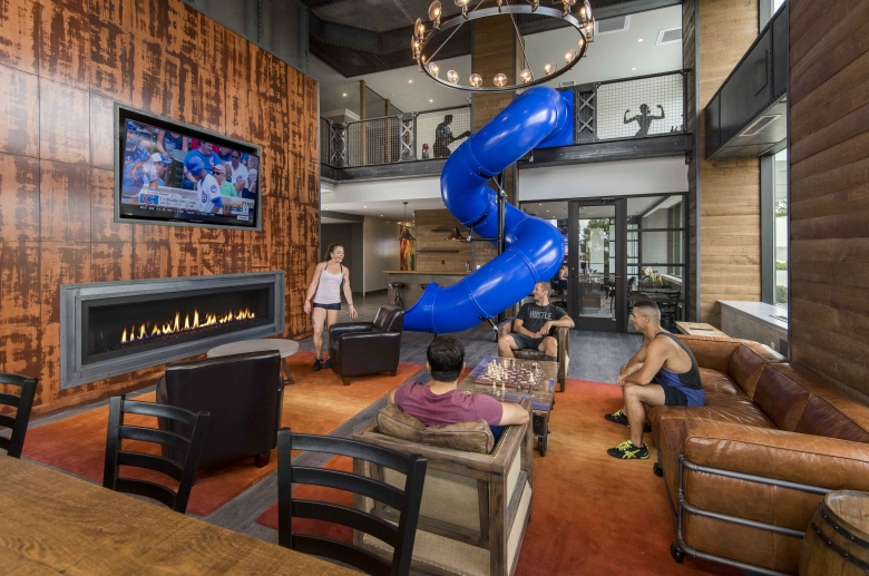Lounge features television, seating, and slide next to the gym