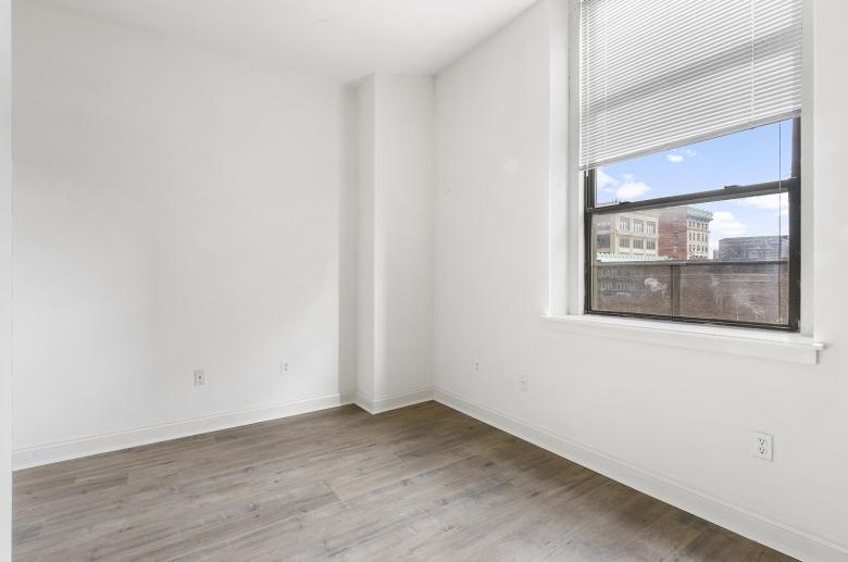 White walls contrasting hardwood floors at 1300 Chestnut Street